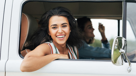 Attractive brunette woman looking outside the car window while traveling