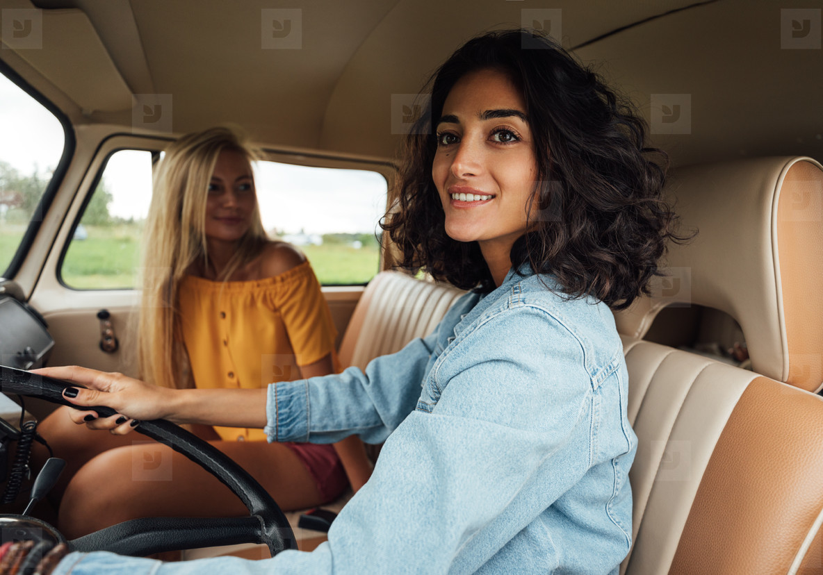 Smiling woman looking outside the car window while driving a van  Women friends enjoying on a road trip