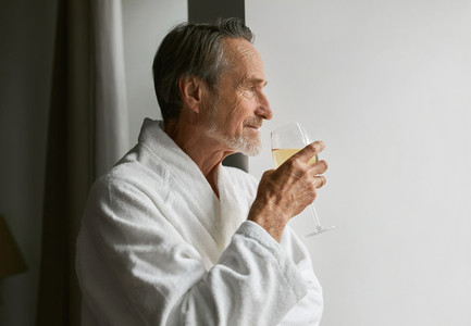 Side view of a caucasian bearded man holding a glass wine wearing bathrobe at hotel room