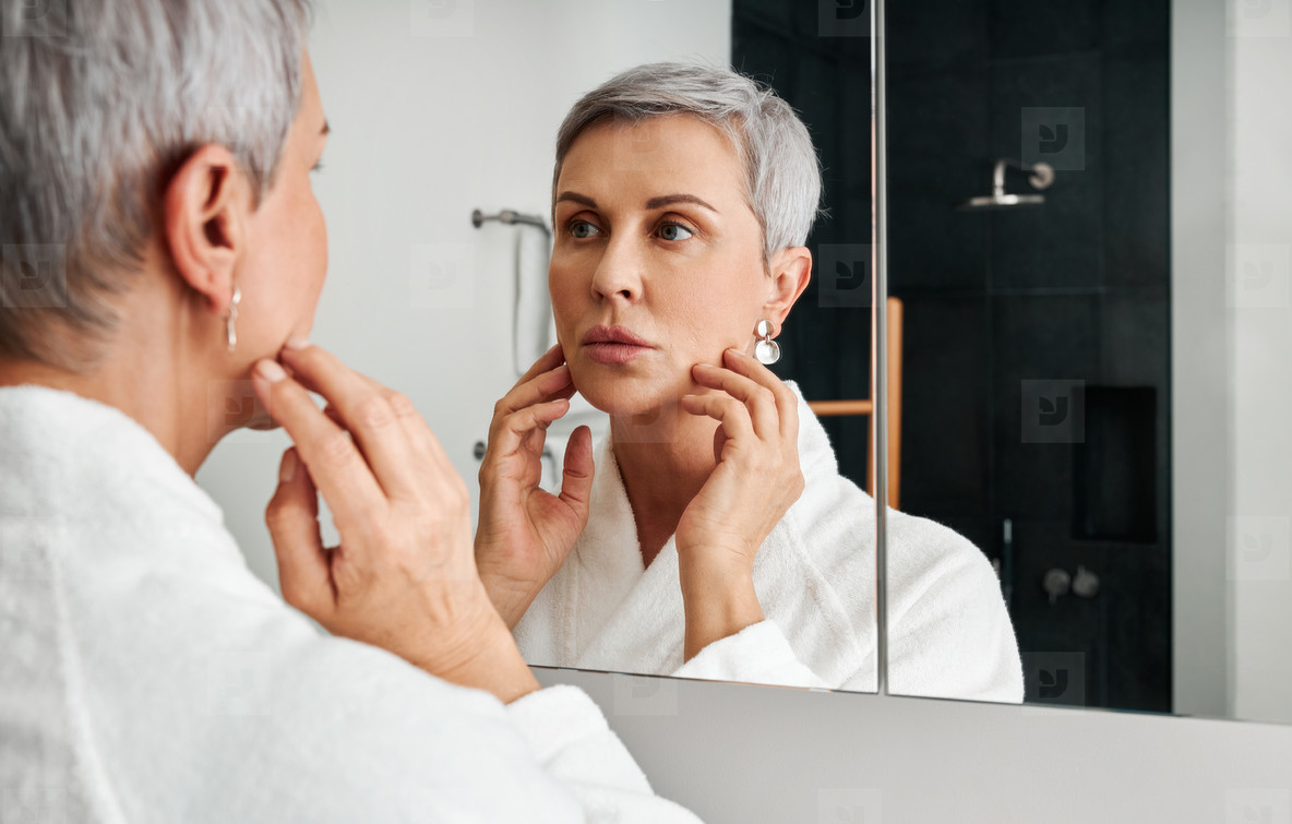 Mature woman with short grey hair touching her face in front of a bathroom mirror