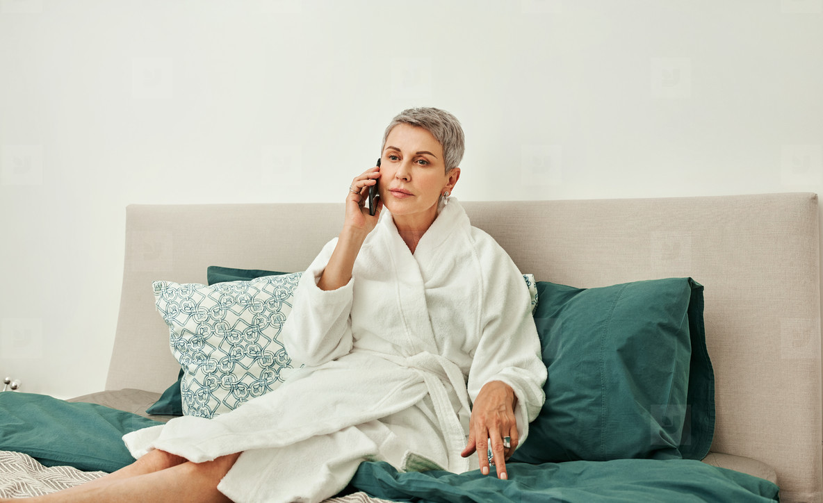 Senior woman with short grey hair talking on a mobile phone from hotel room lying on a bed