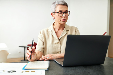 Mature woman looking on laptop screen holding a pen