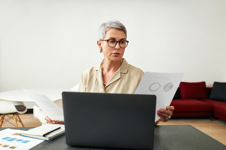 Mature woman wearing eyeglasses holding documents in hands while sitting at home