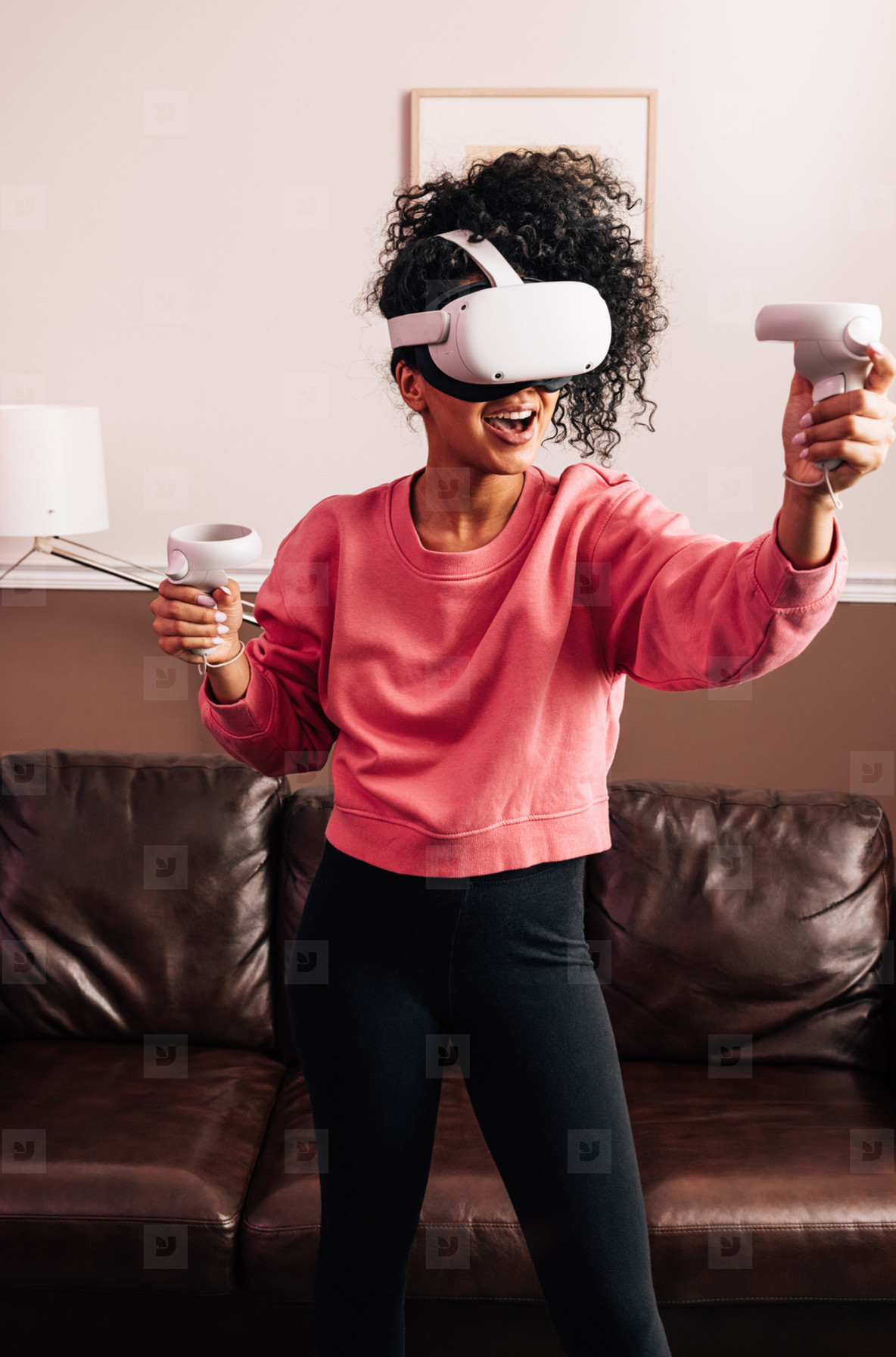Woman with VR goggles and controllers in living room