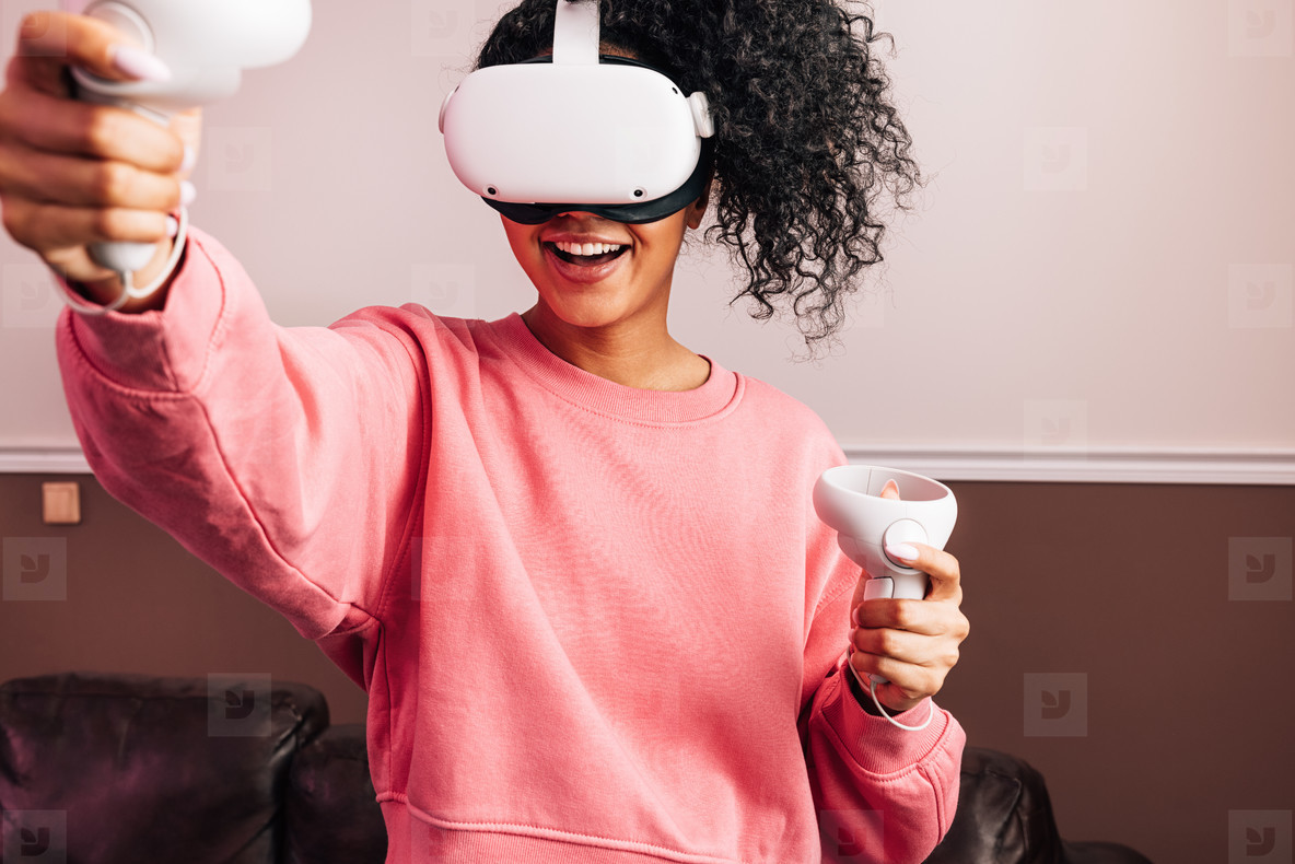 Young African American female in VR goggles and with joysticks experiencing augmented reality at home