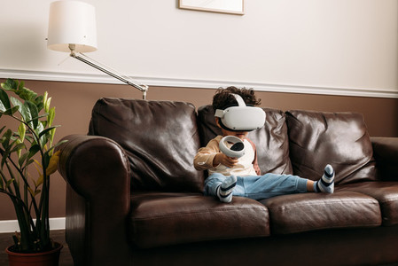 Little boy playing virtual reality game while sitting on sofa in living room