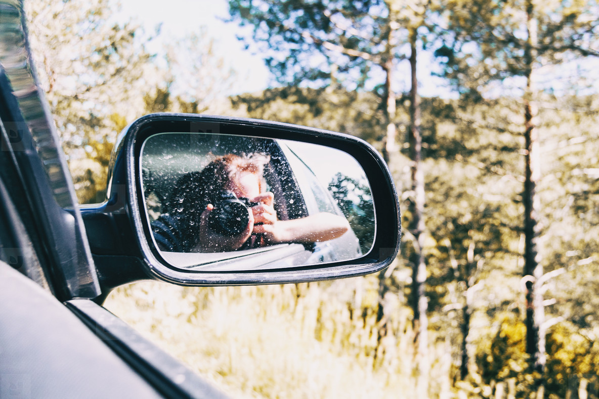 Selfie of a girl in the rear view of the car while the car is running