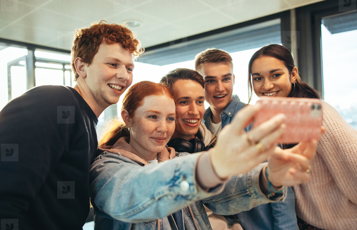 Smiling students clicking selfies in high school