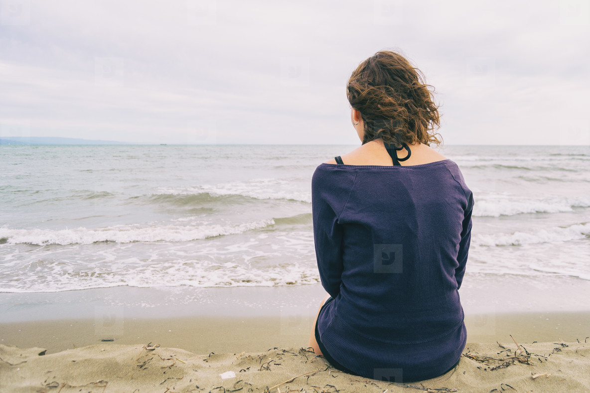 girl sitting on the sand on the shore of the beach looking at the horizon of the sea