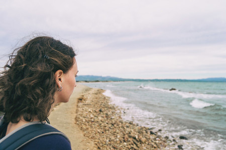 girl looking at the sea on a cloudy and sad day