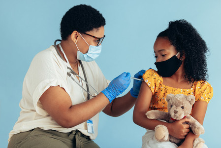 Doctor giving vaccination injection to girl