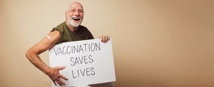 Cheerful senior holding a banner with vaccination saves lives