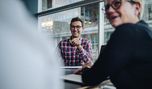Happy businessman in team meeting