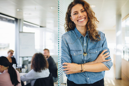 Successful businesswoman standing outside board room