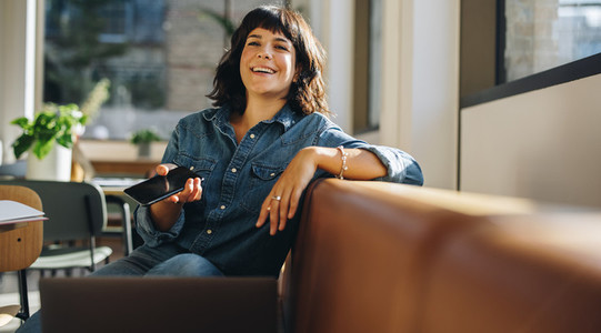 Happy freelancer sitting on sofa in coworking space