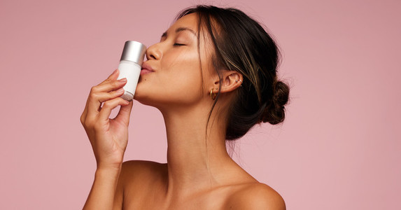 Attractive woman kissing a natural skincare product
