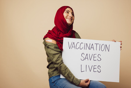 Muslim woman in hijab holding Vaccination saves lives banner