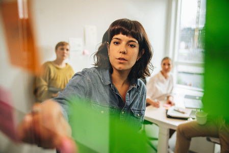 Woman discussing new ideas with team using sticky notes