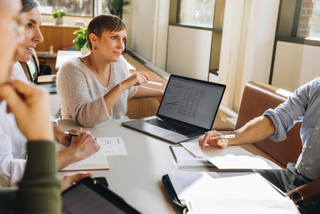 Businesswoman explaining financial details on laptop in meeting