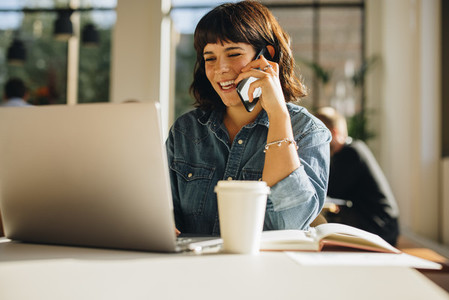 Happy businesswoman talking on mobile phone and using laptop