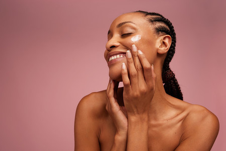 Woman applying face cream and smiling