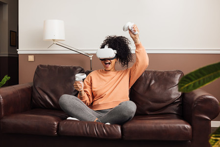 Excited female gamer using virtual reality headset while sitting in room on a couch