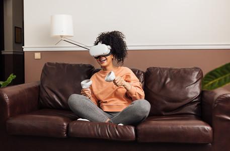 Cheerful woman wearing VR glasses holding joysticks