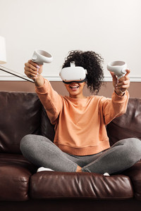 Young happy woman sitting on couch using VR set