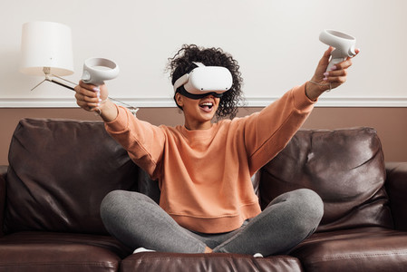 Cheerful mixed race woman sitting on a couch with VR headset