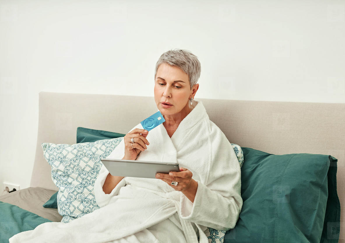 Senior woman shopping online while lying on a bed in hotel room