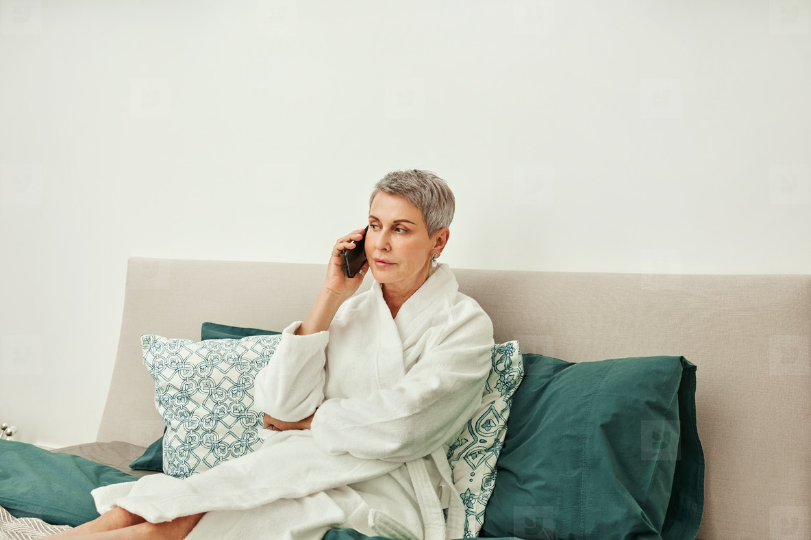 Mature woman in a bathrobe talking on mobile phone while lying on a bed in hotel room