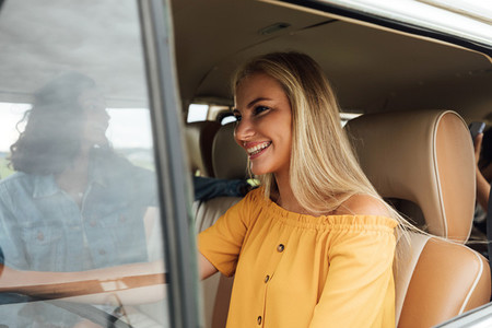 Smiling blond woman driving a camper van going on a road trip with girlfriends