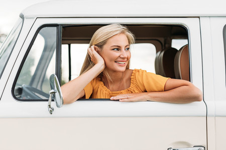 Beautiful young woman looking out of the car enjoying a great time while traveling