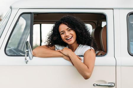 Attractive mixed race woman enjoying road trip looking at camera