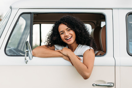Attractive mixed race woman enjoying road trip looking at camera