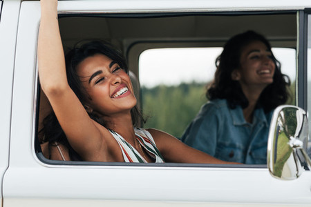 Young laughing woman putting her hand out of a car having fun during road trip