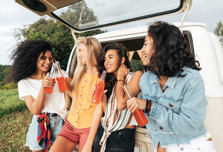 Group of diverse female friends toasting bottles near camper van  Four women enjoying road trip