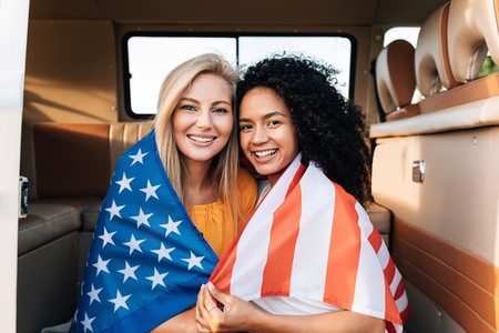 Cheerful female friends sitting together in a camper van with an American flag  Young women enjoying the 4th of July holiday