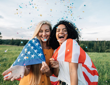 Two happy women standing outdoors under confetti with USA flag
