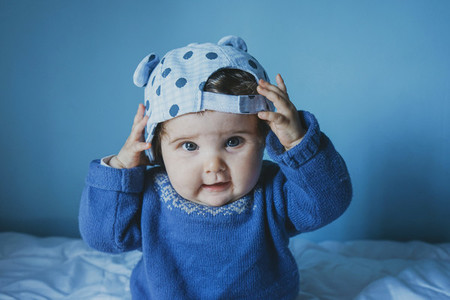 Little baby playing with a cap