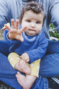 Little baby portrait sitting on his dad legs