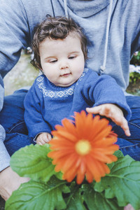 Little baby discovering a huge flower for first time
