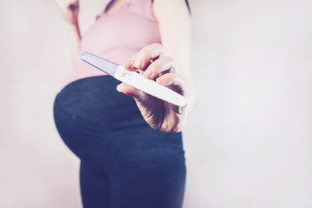 Woman holding a positive pregnancy test