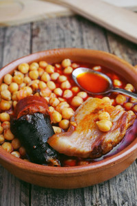 Chickpeas  sausage and bacon in a crockpot by wooden spoon and f