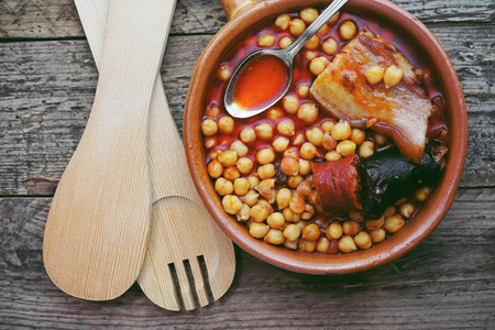Flat of chickpeas  sausage and bacon in a crockpot by wooden spo