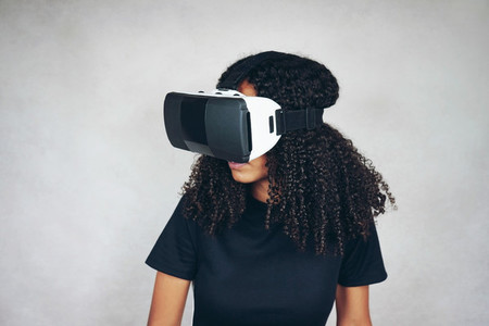 A beautiful young black woman with curly afro hair wears virtual