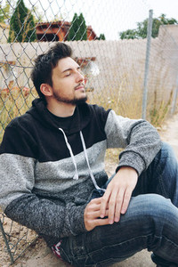 A young attractive man in calm sitting on ground and a outdoor f