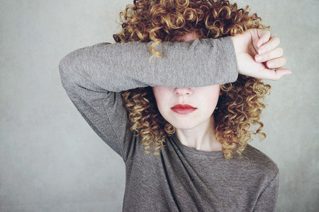 Close up of a beautiful and young woman with curly blonde hair c