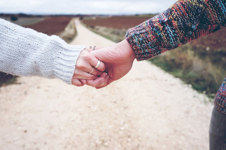 Closeup of a young couple held hands showing their engagement in