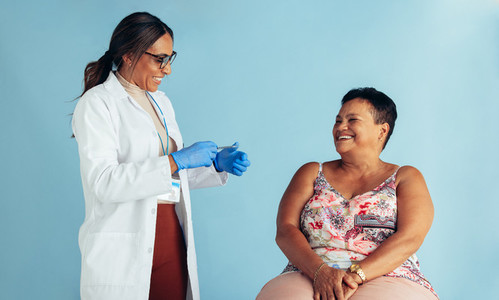 Doctor with senior woman smiling during vaccination